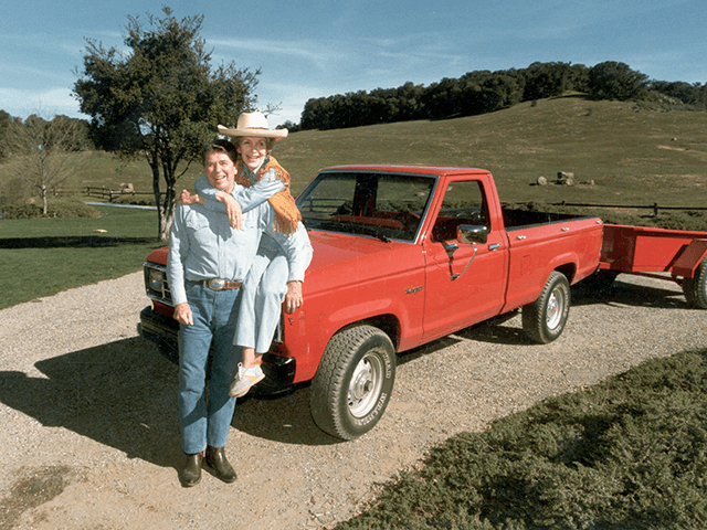 February 1985: A full-length portrait of United States president Ronald Reagan and First Lady Nancy Reagan, who is sitting on the hood of a red 1985 Ford Ranger pick-up truck with her arms around her husband, at their ranch (Rancho del Cielo) near Santa Barbara, California. (Photo by Hulton Archive/Getty …