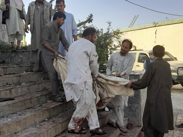 Afghans carry the dead body following a bombing in Kunduz province northern Afghanistan, Friday, Oct. 8, 2021. A powerful explosion in a mosque frequented by a Muslim religious minority in northern Afghanistan on Friday has left several casualties, witnesses and the Taliban's spokesman said. (AP Photo/Abdullah Sahil)
