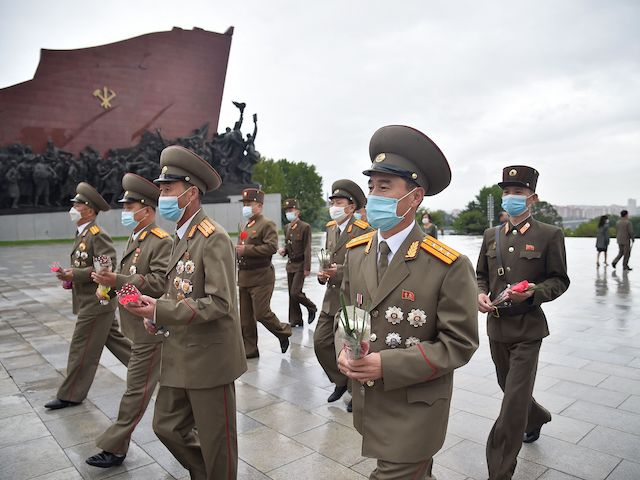North Korean military officials prepare to bow as they arrive to pay their respects before the statues of late North Korean leaders Kim Il Sung and Kim Jong Il at Mansu Hill, as the country marks the 76th founding anniversary of the Workers' Party of Korea, in Pyongyang on October 10, 2021. (Kim Won Jin/AFP via Getty Images)