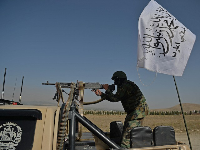 A Taliban fighter stands guard in a vehicle near the venue of an open-air rally in a field on the outskirts of Kabul on October 3, 2021, as the Taliban supporters and senior figures held their first mass rally in a show of strength as they consolidate their rule of Afghanistan. (Hoshang Hashimi/AFP via Getty Images)