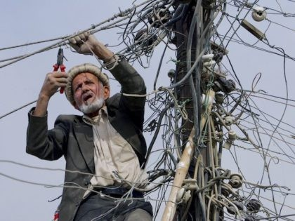 Feda Mohammed, an electrician with Bibimahro power plant, cuts old power lines to improve the electricity in a residential neighborhood November 2, 2006 in Kabul, Afghanistan. (Paula Bronstein/Getty Images)