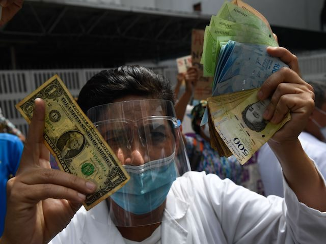 A health worker wearing a face mask and shield holds a one dollar bill in one hand and its equivalent in Bolivar bills -his salary- in the other, during a protest for the lack of medicines, medical supplies and poor conditions in hospitals, in Caracas on October 29, 2020, amid …