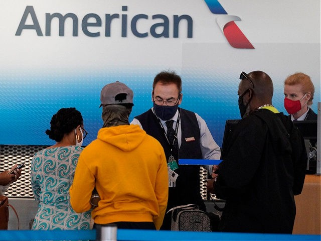 American Airlines employees work at ticket counters in Terminal 3 at O'Hare International Airport in Chicago, Friday, July 2, 2021. (AP Photo/Nam Y. Huh)