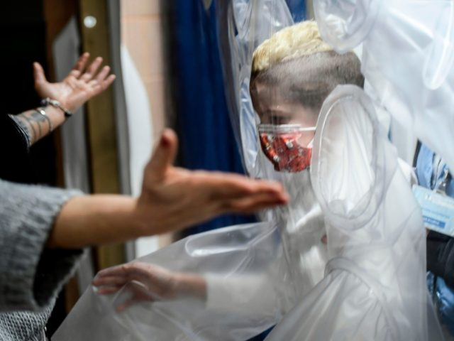A boy hospitalized in the Department of paediatric rehabilitation and developmental disabilities of IRCCS at the San Raffaele hospital in Rome, prepares to hug his mother through a plastic protection to avoid catching the COVID-19 on December 22, 2020. - The San Raffaele in Rome has decided to let children …