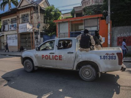 Armed police ride in the back of a truck after the streets of the Haitian capital Port-au-Prince were deserted following a call for a general strike launched by several professional associations and companies to denounce insecurity in Port-au-Prince on October 18, 2021. - A nationwide general strike emptied the streets …