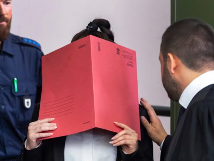 27-year-old German Jennifer W. covers her face as she arrives at a court in Munich, southern Germany, Tuesday, April 9, 2019. The woman is accused of letting a 5-year-old girl she and her husband held as a slave in Islamic State-held territory in Iraq die of thirst. (Peter Kneffel/dpa via …