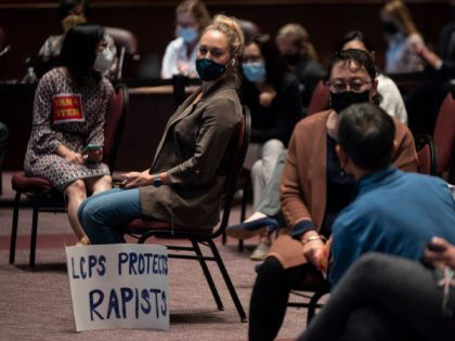 A woman sits with her sign during a Loudoun County Public Schools (LCPS) board meeting in Ashburn, Virginia on October 12, 2021. - Loudoun county school board meetings have become tense recently with parents clashing with board members over transgender issues, the teaching of critical race theory (CRT) and Covid-19 …