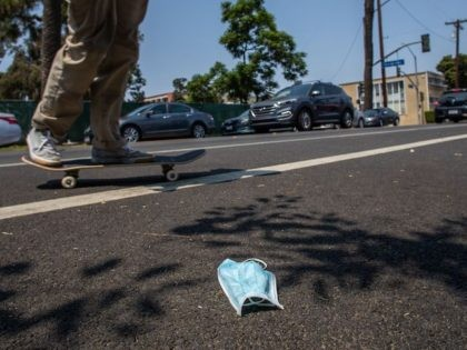 A man rides his skateboard next to a discarded face mask on the street in Long Beach, California on August 22, 2020. - Due to the novel coronavirus, COVID-19, more people wear masks to prevent the spread, more personal protective equipment, or PPE, has been found as litter around the …