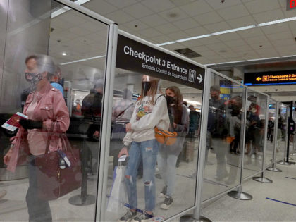 MIAMI, FLORIDA - SEPTEMBER 03: Travelers wait in line at the TSA checkpoint in the Miami International Airport before starting the Labor Day weekend on September 03, 2021 in Miami, Florida. The Centers for Disease Control and Prevention recommended that people unvaccinated against the Covid-19 virus should not travel this …