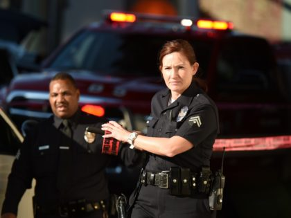 A female police officer uses police tape to cordon off an area outside a Jack in the Box restaurant in Hollywood, California, January 31, 2017, after police shot and killed a knife-wielding suspect inside the restaurant following a series of stabbing in the vicinity. Authorities said a person described only …